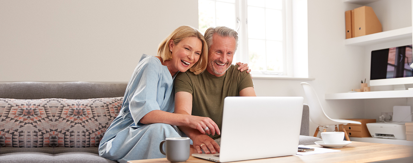Happy middle aged couple looking at a laptop together