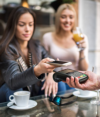 Ladies at a restaurant paying with a smartphone