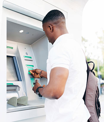 Man at an ATM withdrawing money
